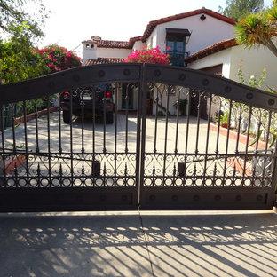 Ejemplo de fachada blanca, mediterránea, de tamaño medio, de dos plantas, con revestimiento de estuco y tejado a dos aguas