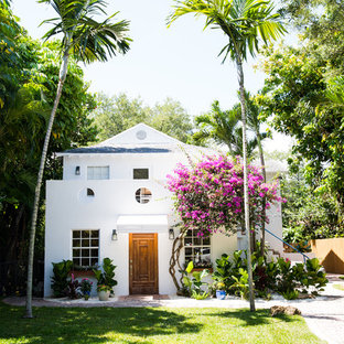 Mid-sized coastal white two-story stucco gable roof photo in Miami with a shingle roof