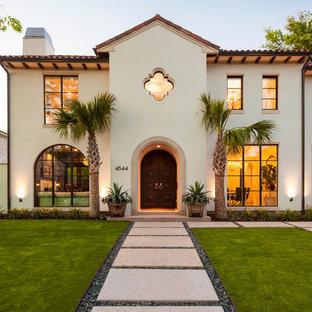 Diseño de fachada beige, mediterránea, de dos plantas, con revestimiento de estuco