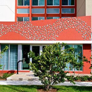 Aménagement d'une très grande façade de maison multicolore contemporaine à deux étages et plus avec un toit plat et un toit mixte.