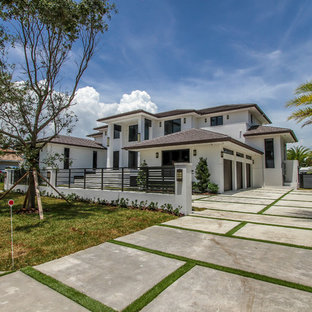 Large modern white two-story stucco exterior home idea in Miami with a shingle roof