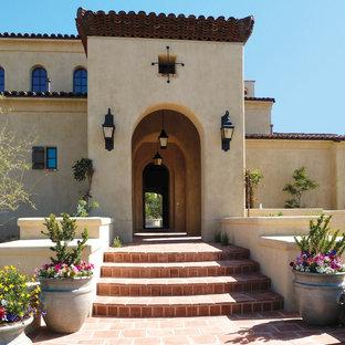 Modelo de fachada de casa beige, mediterránea, grande, de dos plantas, con revestimiento de adobe, tejado a dos aguas y tejado de teja de barro