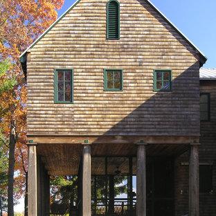 Foto de fachada rústica con revestimiento de madera y tejado a dos aguas