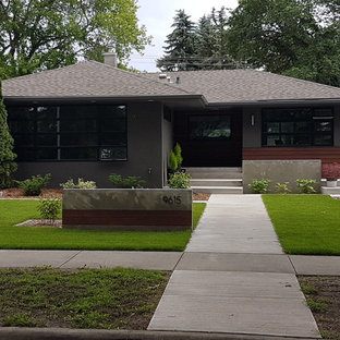 Mid-sized 1960s gray one-story concrete house exterior photo in Edmonton with a hip roof and a shingle roof