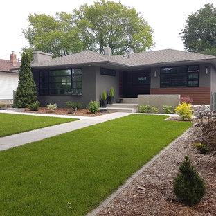 На фото: одноэтажный, серый частный загородный дом среднего размера в стиле ретро с облицовкой из бетона, вальмовой крышей и крышей из гибкой черепицы