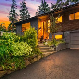 Imagen de fachada gris, retro, de tamaño medio, a niveles, con revestimiento de madera y tejado a dos aguas