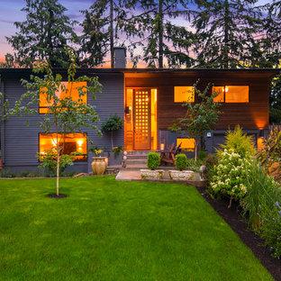 Imagen de fachada gris, actual, de tamaño medio, a niveles, con revestimiento de madera y tejado a dos aguas