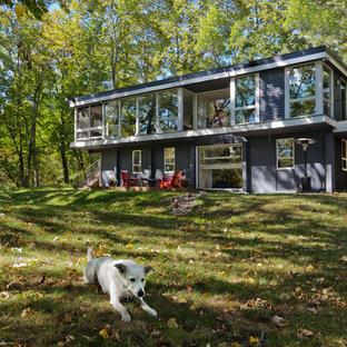 Exemple d'une façade de maison grise rétro à niveaux décalés avec un revêtement en panneau de béton fibré.