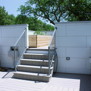Imagen de fachada blanca, vintage, de tamaño medio, a niveles, con revestimiento de aglomerado de cemento