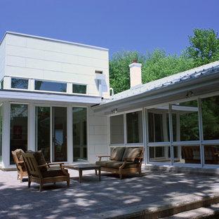 Foto de fachada blanca, vintage, de tamaño medio, a niveles, con revestimiento de aglomerado de cemento
