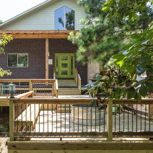 Imagen de fachada de casa multicolor, vintage, de tamaño medio, a niveles, con revestimiento de ladrillo, tejado a dos aguas y tejado de metal