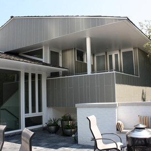 Foto de fachada gris, retro, a niveles, con revestimiento de aglomerado de cemento