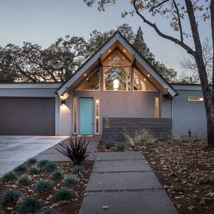 Example of a large 1960s gray one-story stucco exterior home design in Portland with a shingle roof