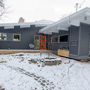 Стильный дизайн: одноэтажный, серый частный загородный дом среднего размера в стиле ретро с облицовкой из винила и мансардной крышей - последний тренд