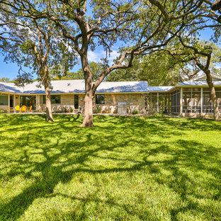 Foto de fachada de casa beige, vintage, extra grande, de una planta, con revestimientos combinados, tejado a dos aguas y tejado de metal
