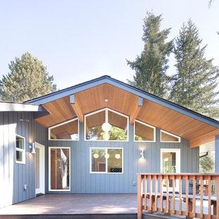 Imagen de fachada de casa gris, retro, de tamaño medio, de dos plantas, con revestimiento de madera, tejado a dos aguas y tejado de teja de madera