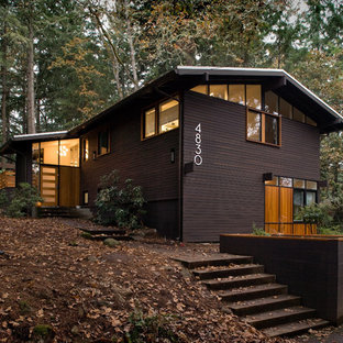 This is an example of a midcentury exterior in Portland with wood cladding and a pitched roof.