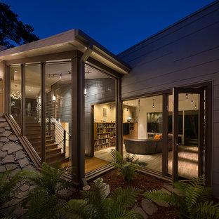 Cette image montre une grand façade de maison grise vintage à un étage avec un revêtement en panneau de béton fibré et un toit plat.