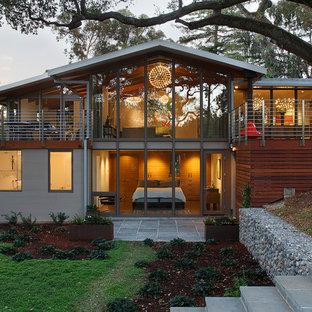 Imagen de fachada gris, vintage, grande, de dos plantas, con revestimientos combinados y tejado plano