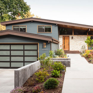 Inspiration for a mid-sized 1960s blue one-story stone exterior home remodel in Seattle