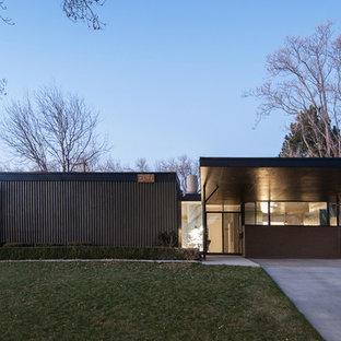 На фото: дом в стиле ретро с облицовкой из металла и плоской крышей