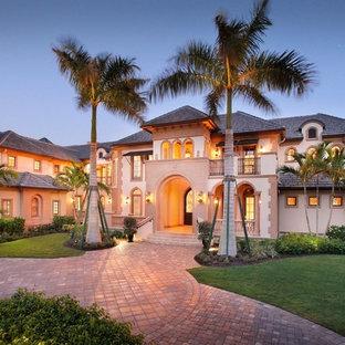 Modelo de fachada beige, retro, extra grande, de tres plantas, con revestimiento de estuco y tejado a cuatro aguas