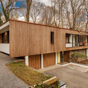 Mid-sized midcentury modern beige two-story wood flat roof photo in New York
