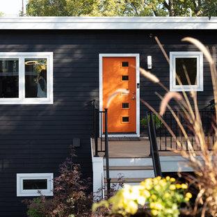 Diseño de fachada de piso gris, retro, de tamaño medio, de dos plantas, con revestimiento de vinilo, tejado plano y tejado de teja de madera