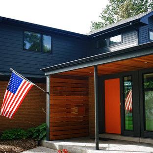 Idée de décoration pour une façade de maison bleue vintage de taille moyenne et à un étage avec un revêtement mixte et un toit à deux pans.
