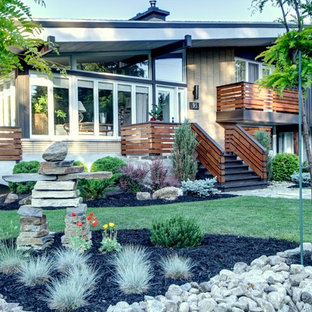 Inspiration for a large 1960s beige two-story brick exterior home remodel in Montreal