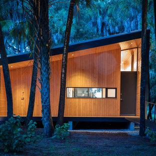 Réalisation d'une petite façade de maison multicolore design de plain-pied avec un toit en appentis et un toit en métal.