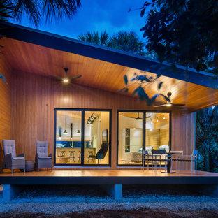 Пример оригинального дизайна: маленький, одноэтажный, разноцветный частный загородный дом в современном стиле с облицовкой из металла, односкатной крышей и металлической крышей