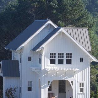 Foto de fachada blanca, costera, de tamaño medio, de dos plantas, con revestimiento de madera