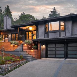 Diseño de fachada de casa gris, actual, grande, de dos plantas, con revestimiento de madera y tejado a cuatro aguas