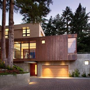 Imagen de fachada marrón, moderna, de tamaño medio, de tres plantas, con revestimiento de hormigón
