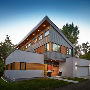 Design ideas for a large contemporary two-storey white house exterior in Edmonton with mixed siding and a shed roof.
