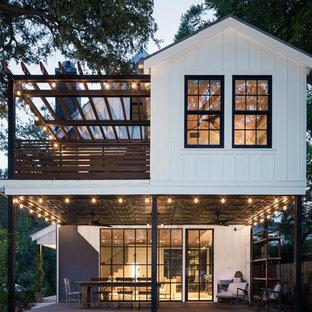 На фото: двухэтажный, белый частный загородный дом в стиле кантри с двускатной крышей с