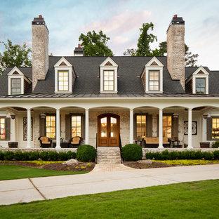Modelo de fachada de casa blanca, campestre, de tamaño medio, de dos plantas, con revestimientos combinados, tejado a dos aguas y tejado de teja de madera