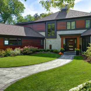 Diseño de fachada de casa multicolor, actual, grande, de dos plantas, con revestimiento de ladrillo, tejado a dos aguas y tejado de teja de madera