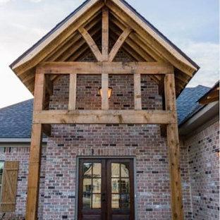 Foto de fachada de casa roja, de estilo americano, de tamaño medio, a niveles, con revestimiento de ladrillo, tejado a cuatro aguas y tejado de teja de madera