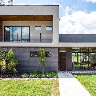 Ispirazione per la facciata di una casa unifamiliare grande beige contemporanea a piani sfalsati con rivestimenti misti e tetto piano