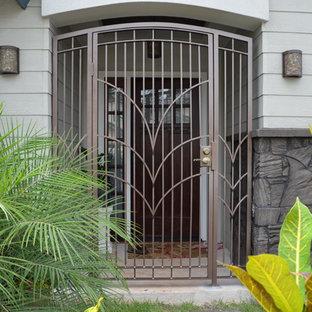Foto på ett mellanstort tropiskt beige hus, med allt i ett plan och stuckatur