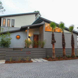 Design ideas for a contemporary two-storey grey exterior in Miami with mixed siding and a shed roof.