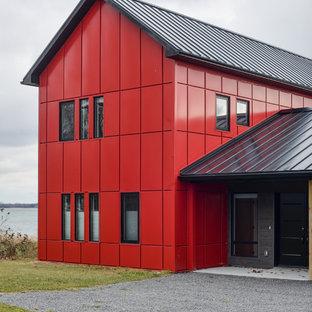 Foto de fachada roja, actual, de tamaño medio, de dos plantas, con revestimientos combinados y tejado a dos aguas