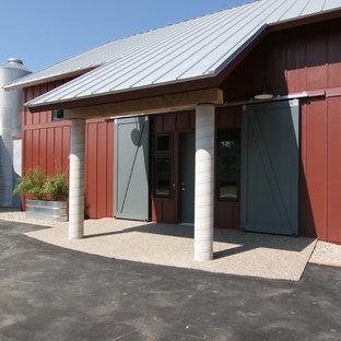 Imagen de fachada roja, campestre, de tamaño medio, de dos plantas, con revestimiento de aglomerado de cemento