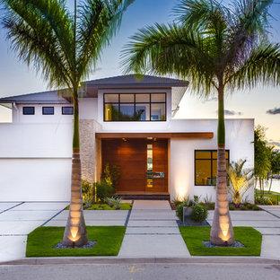 Imagen de fachada blanca, tropical, de dos plantas, con revestimiento de estuco y tejado a cuatro aguas