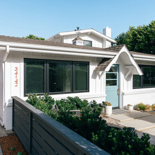 Example of a small coastal white two-story wood gable roof design in Orange County with a shingle roof