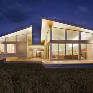 Идея дизайна: двухэтажный, серый частный загородный дом в стиле модернизм с облицовкой из металла и односкатной крышей