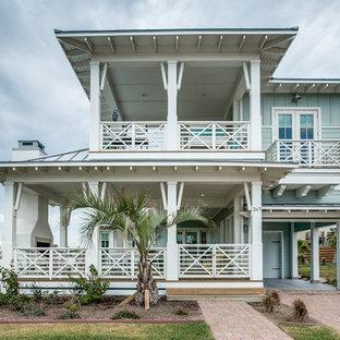 Inspiration för maritima blå hus, med två våningar, valmat tak och tak i metall