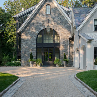 На фото: трехэтажный, серый, большой частный загородный дом в стиле современная классика с облицовкой из камня, двускатной крышей и крышей из гибкой черепицы